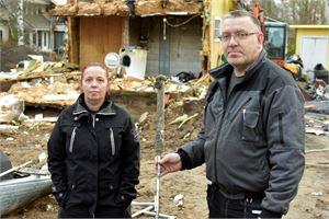 Harriet ja Juhani Mäkelä talonsa raunioilla. Juhani Mäkelällä on kädessään pesuri, josta palo sai alkunsa.