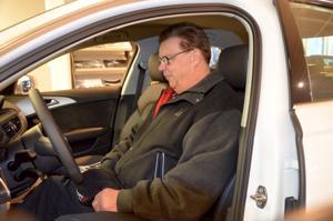 Tarmo Kokko testamaassa uuden auton penkkiä Ylivieskan autokaupan  vuoden ensimmäisessä autonäyttelyssä.