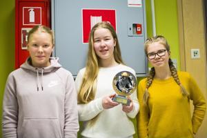 Venla Peräaho (vas.), Pauliina Tölli ja Helmi Eskola pokkasivat komean, palomiehen kuvalla varustellun palkinnon aluefinaalin voitosta. Se tulee päätymään Niva-Kaijan koululla kunniapaikalle vitriiniin.