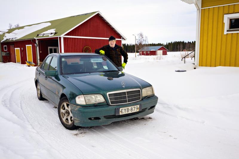 Martti Puskala ja miljoona-Mersu. Puskala teetti aurinkolippaan ajomatkasta kertovan tarran mainostoimistossa.