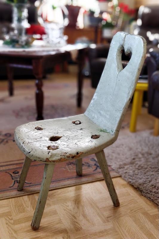 Antiikkinen tuoli toimittaa jalkajakkaran virkaa telsua katsellessa ja käsitöitä tehdessä.