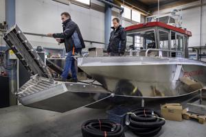 Kewatec AluBoatin myyntipäällikkö Jan Wargh ja projektipäällikkö Jonas Krokvik Kymenlaaksoon matkalla olevan pelastusaluksen kannella. Hydraulisen keulaportin jatkoksi laskettava silta helpottaa rantautumista.