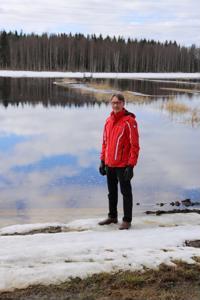 Mikko Hänninen takapihallaan. Lumen reunassa näkyy joen rantaan nostettu laituri.