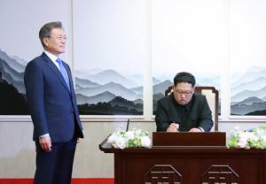 Etelä-Korean presidentti Moon Jae-in odotti vieressä, kun Pohjois-Korean johtaja Kim Jong-un kirjoitti terveisensä vieraskirjaan perjantaina.