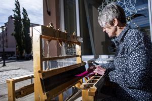 Taito Keski-Pohjanmaan toiminnanjohtaja Tuula Puoskari näyttää, miten kutominen onnistuu ulkona auringonpaisteessa yhtä lailla kuin sisätiloissa.