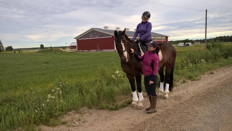 Ratsastuskilpailu järjestetään kuvassa näkyvällä Stall Överbyn alueella. Hevosen selässä istuu kilpailunjohtaja Janika Kupila ja vierellä seisoo yrittäjä Eeva-Maija Jakobsson.