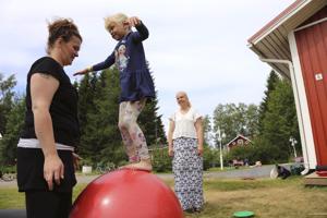 Nelli Koski kokeilee sirkuspallon päällä tasapainoilua Elina Holopaisen avustuksella. Satu Koski (oik.) valitsi kierrettäviä kirppiskohteita kartasta myös sen mukaan, mikä lapsia kiinnostaisi.
