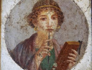 Nuori nainen ikuistettiin vahataulun ja kirjoituspuikon eli styloksen kanssa. Pompejilainen maalaus on esillä Napolin arkeologisessa museossa.