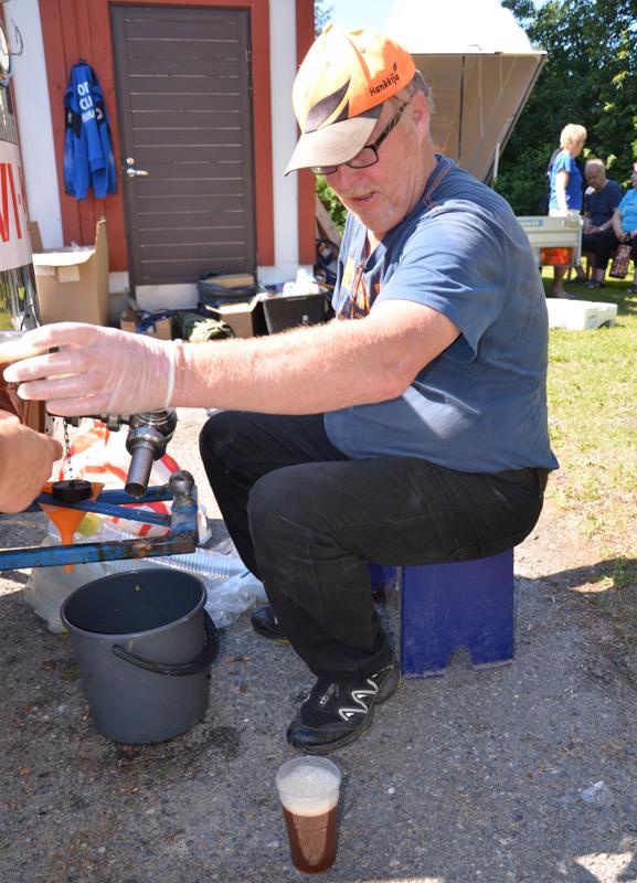 Himankalainen Paavo Tiinanen laittaa sahtia tuoppeihin tiuhaan tahtiin. Helteisellä ilmalla suosittu paikallisjuoma maistuu.