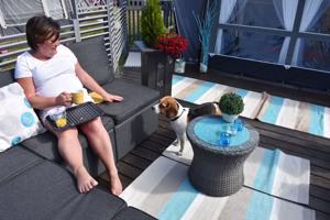 Päivi Niemelä nauttii aamiaista vaunun terassilla seuranaan Muska-koira.