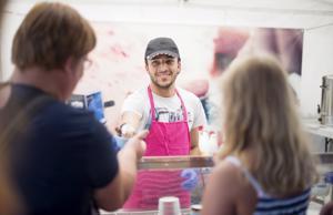 Juusef Lateh ojentaa tuoreen jäätelöannoksen asiakkaille. Lateh kertoo, että jäätelön valmistus on vaikeampaa kuumassa säässä.