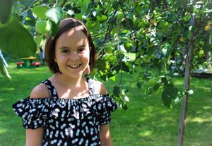 Taekwondoa, balettia ja voimistelua harrastava Sara kiipeili kesälomareissulla mummulan omenapuissa.