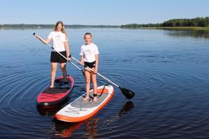 Laura Alaspää ja Saana Koskimäki opastavat vuokraajia SUP-lautailussa Räyringinjärvellä.