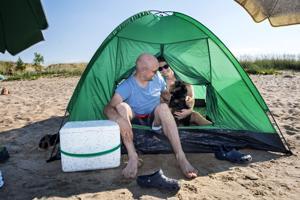 Teemu ja Meri Korpikoski toivat rannalle varjoja, jotta Bossa-koirakin jaksaisi helteessä.