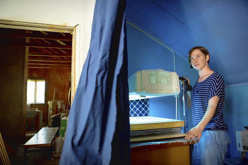 Anu Martikkala valottaa pimiössä seuloja, joita hän tarvitsee äitiyspakkauksen tuotteiden kissakuvioinnin painantaa varten.