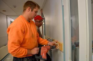 Visalan tiloja kunnostetaan kiireellä päiväkotikäyttöön. Joel Ekdahl ja Tarmo Pulli Rakennuspalvelu Salmelasta asentavat naulakoita lapsille sopivaan korkeuteen.