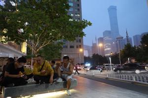 Miehet selailevat puhelimiaan Kiinan pääkaupungin Pekingissä liike-elämän solmukohdaksi kutsutulla alueella 13. elokuuta 2018. Kiina on viime vuosina kiristänyt tuntuvasti verkkosensuuria.