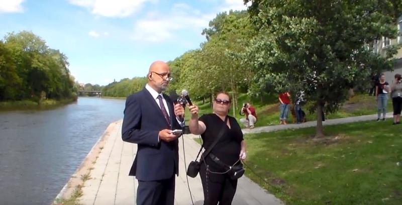 Kuvankaappaus videolta, jossa Mauri Peltokangas on pitämässä puhettaan 118 Kukkavirta-tapahtumassa. Mikrofonia pitelee Terhi Kiemunki.