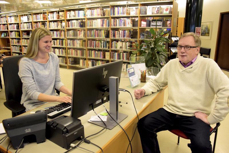 Lina Granqvist-Björkskog hoitaa kaupunginkirjaston tietojärjestelmiä. Kirjastonjohtaja Leif Björkskog istahtaa vaihteeksi asiakkaan tuolille.