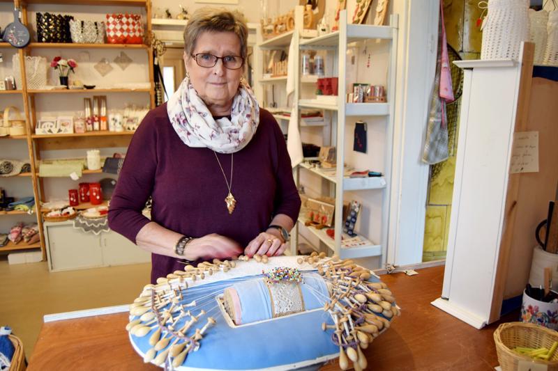 Gitta Strömbäck on tuonut käsityöläispuotiin esille myös nypläystyynynsä ja esittelee, miten nyplätään.