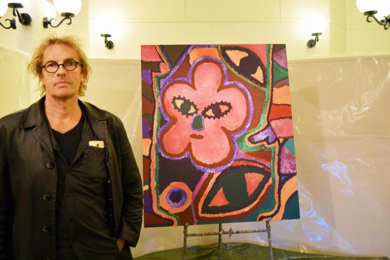 Andy Sundqvist ja keskeneräinen työ, jonka hän viimeisteli näyttelyn avajaisissa. Kukkia ja silmiä on monissa hänen tauluissaan.