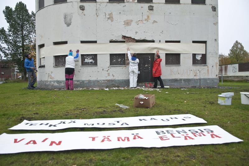Keski-Pohjanmaan kansanopiston kuvataidelinjan opiskelijat tapetoivat funkkistyylistä huoltamorakennusta Kokkolassa.