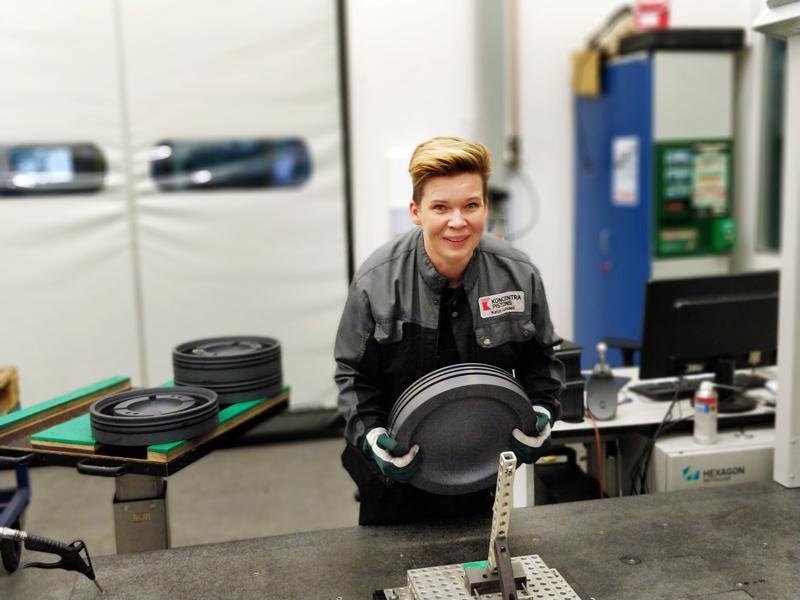 Katja Lundell siirtää kaksikymmenkiloista männän yläkappaletta 3D-mittaukseen Koncentra Pistonsilla.
