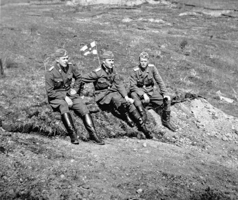 SS-miehet tauolla. Sotilaspastori Kalervo Kurkialan (keskellä) vieressä huilaavat Erich Lange ja Lennart Wallén.
