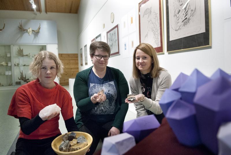 Mari Mäenpää (vas.), Heidi Pokela ja Aija Isosaari käsissään erilaisia kvartseja. Etualalla paperista tehty jättiametisti.