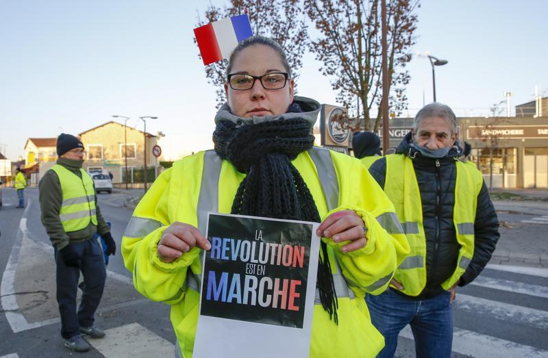 """""""Vallankumous liikkeessä"""" ilmoitti keltaliiviprotestoija kyltissään. Teksti on muunnos presidentti Emmanuel Macronin puolueen nimestä."""