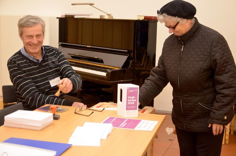 Vaalitoimitsija Ari Mehtälä leimaamassa Aino Ylitalon äänestyslippua.
