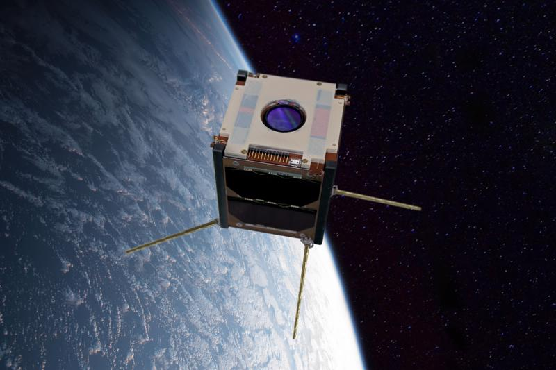Hahmotelma Suomi 100 -satelliitista Maata kiertämässä. Kokeellinen 3D-tulostettu muoviosa on selvästi näkyvissä satelliitin etuosassa. Sen sisällä ovat radiotutkimuslaitteen antennit. Kameran linssi näkyy muoviosan keskellä.