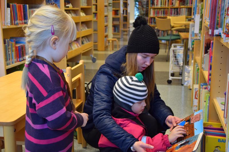 Benjami Lastikka kurkistaa Puppe-kirjan luukkuihin isosiskonsa Jutta Lastikan kanssa, ja Vilja Tikkasta (vas.) kiinnostaa, mitä kuvia luukusta löytyy.