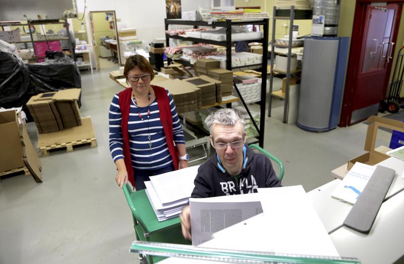 Eke-tuotteella tehdään monipuolisia kirjapainotöitä. Työnjohtaja Kirsti Pekkarinen neuvoo Jarmo Pajukankaalle leikkurin käyttöä.