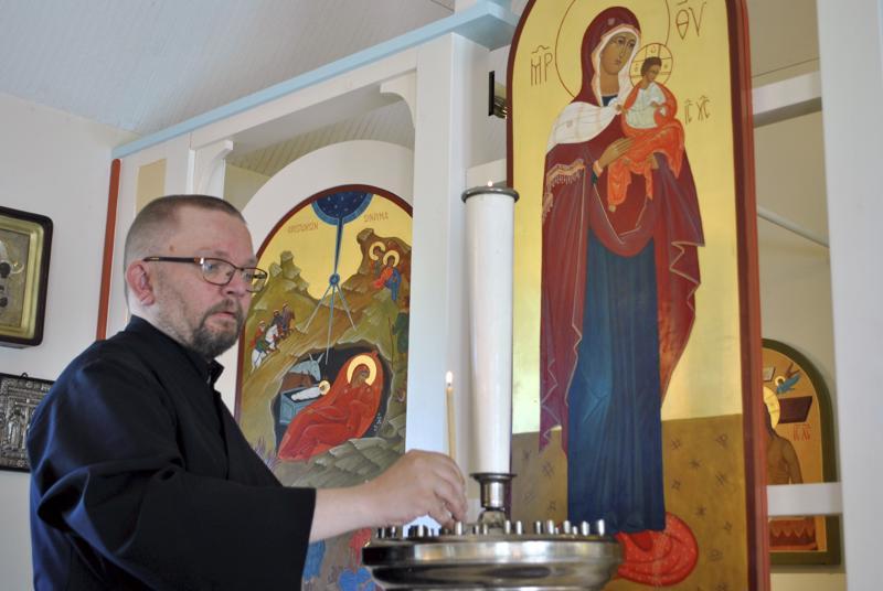 Nivalan Karvoskylän ortodoksikirkon isännöitsijä Jarmo Pylkkönen sytyttämässä lampukkaa ikonostaasin eteen.
