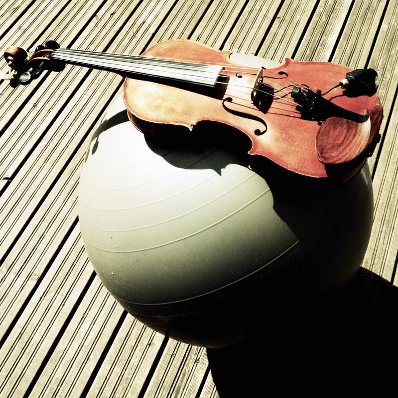 Kuvassa kirjoittajan jumppapallo ja viulu.