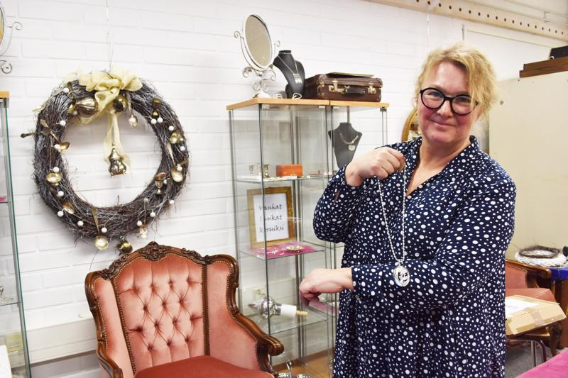 Anni-Riitta Koskela kertoo lusikkakorujen pysyneen suosiossa. Sormusten lisäksi vanhoista hopealusikoista syntyy riipuksia. Taustalla näkyvä joulukranssi on korupajan tuotteilla koristeltu.