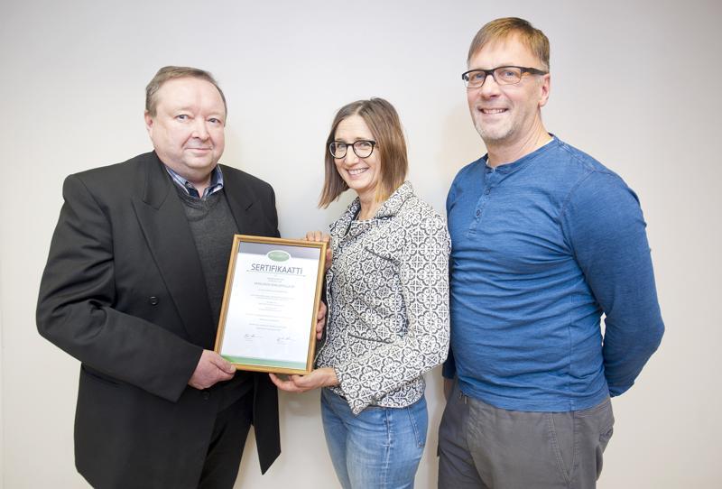 Ari Isohanni (vas.) PKY-Laadun edustajana luovutti sertifikaatin Keskuspesulan Kristiina ja Milko Liedekselle.