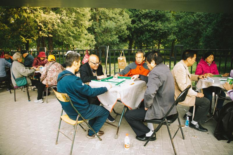Kiinalaiset pelaavat lautapelejä puistoissa pureskellen samalla siemeniä ja hörppäilen teetä termosmukeista.