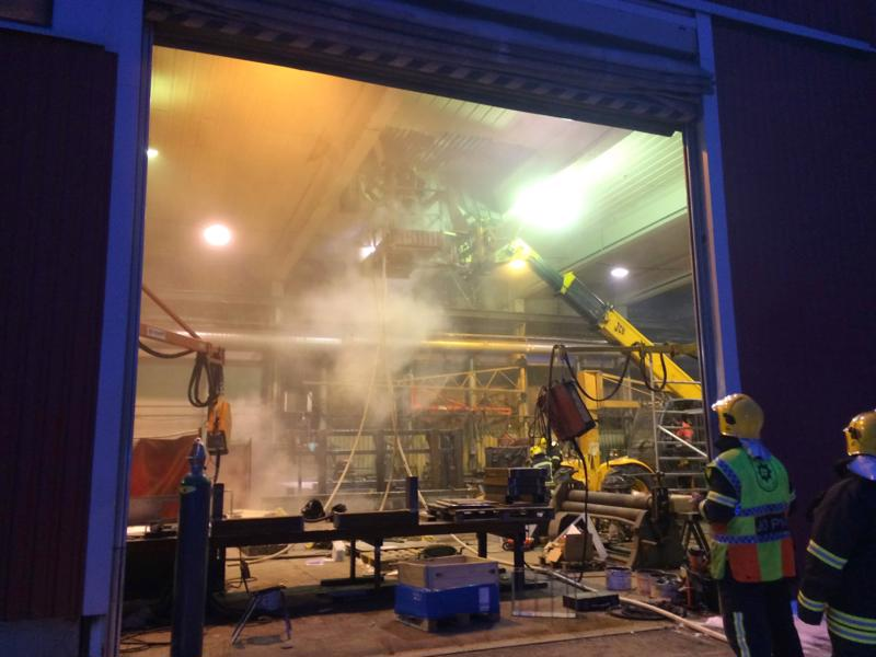 Teollisuusalan yrityksen kattoa puretaan nosturilla.