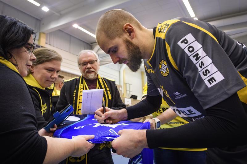 Olli-Pekka Ojansivun paluu Kokkolaan päättyi tappioon. Pelin jälkeen Ojansivulla oli silti aikaa raapustaa nimmari pelipaitaan. Arvontapalkintona ollutta paitaa pitelemässä Jaana Kåla ja taustalla paidan voittanut Hannu Pajunpää.
