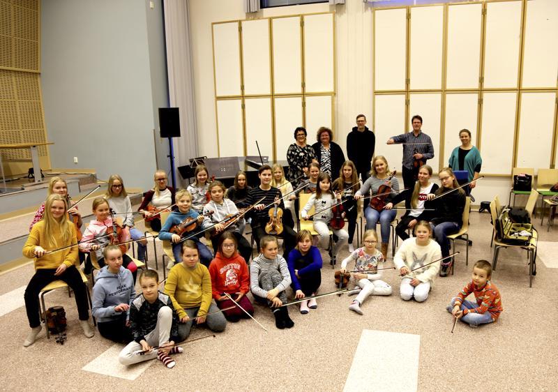 Keski-Pohjanmaan konservatoriossa viulun perusopetuksessa olevia oppilaita sekä taustalla opettajat. Janne Malmivaaralla kädessään jousi.