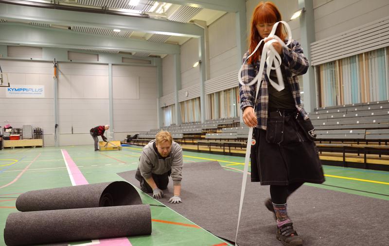 RSA-messujen graafinen johtaja Viola Kantola ja rakennuspäällikkö Juuso Heino vetivät messumattoa lattiaan torstaina iltapäivällä liikuntakeskuksessa.