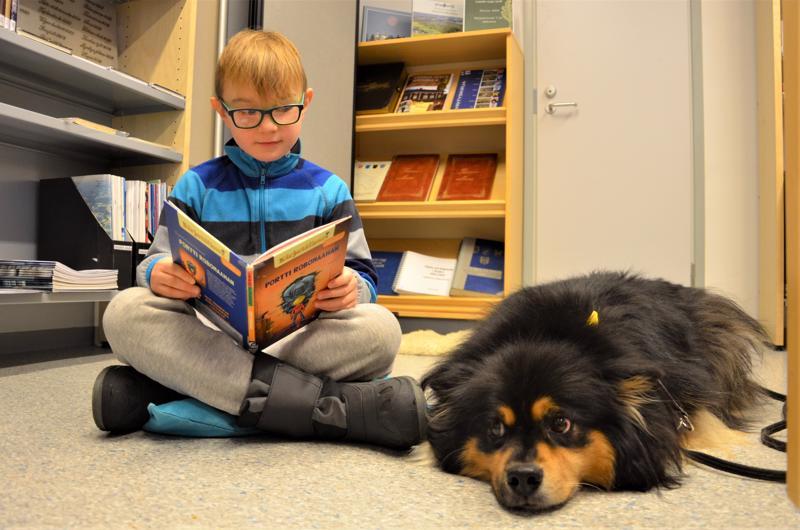 Lukukoira Mesta kuunteli tarkkaavaisena, kun Matti Torppa luki robottikirjaa Vetelin kirjastossa.