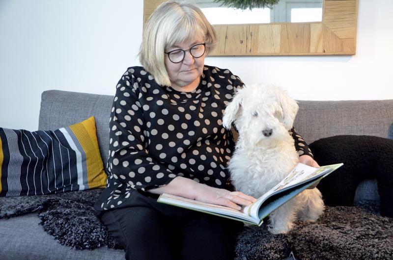 Maija Hietala valitsee kirjahyllystä Mauri Kunnaksen Seitsemän koiraveljestä ja tuleva lukukoira Fanni asettautuu kuulolle.