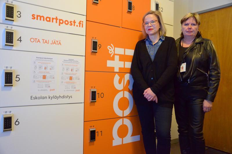 Eskolan pakettiautomaatti sijaitsee Eskola-talon eteisessä, esittelevät kyläyhdistyksen projektityöntekijä Miia Tiilikainen (vas.) sekä Postin Pohjanmaan aluepäällikkö Sirkka-Liisa Korpi. Siinä on 17 erikokoista lokerikkoa.