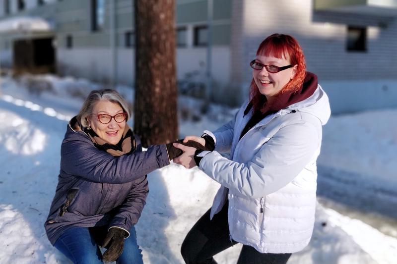 – Hyvä ystävä voi toisen  puolesta istua vaikka lumi- hangessa, nauraa Irma  Salonen. Vappu Moisio  auttaa ylös.