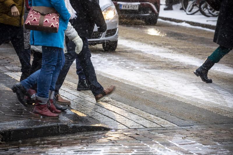 Jalankulkijoita ja autoja Pohjoisesplanadilla Helsingissä tammikuun lopulla.