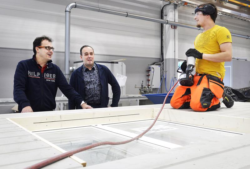 Seinäelementtejä valmistuu linjastolla nopsaan. Markus Göös ja Petri Silver jututtavat Eero Veijalaista. Elementtitehtaan työntekijät tulevat lähialueen kunnista. Uusien ammattilaisten löytäminen on haastellista, Markus Göös sanoo.