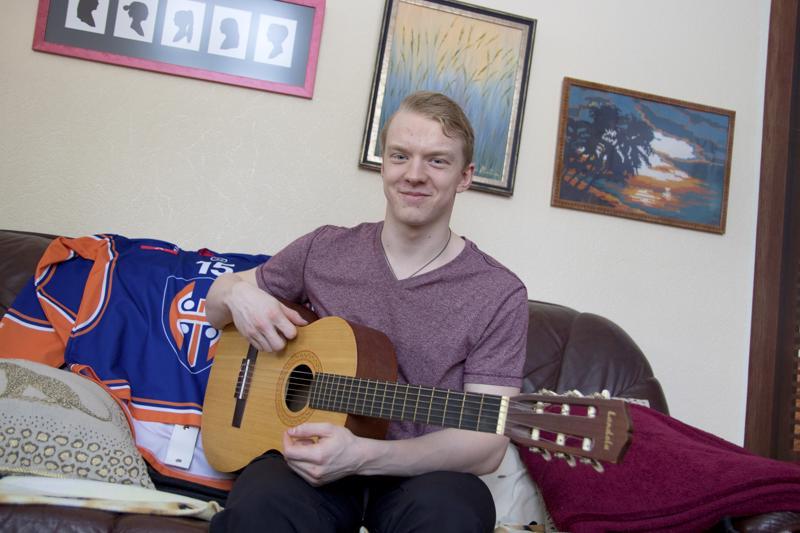 Toni Utunen rentoutuu soittelemalla kitaraa.